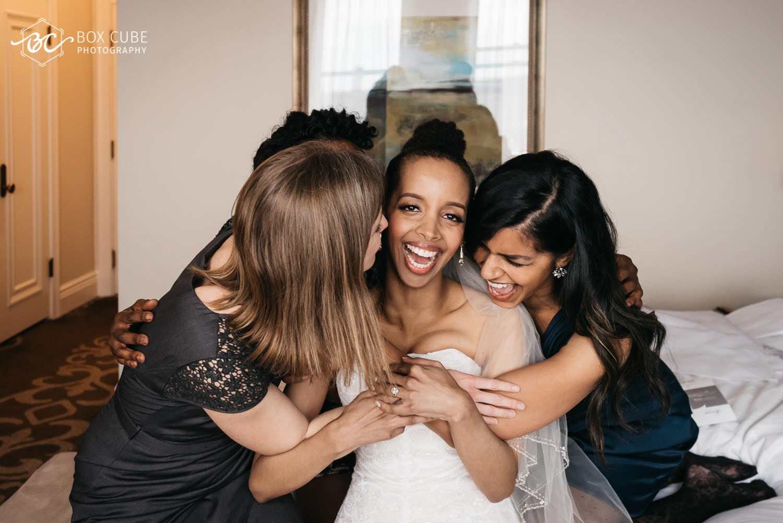 Bridesmaids hugging the bride at the hotel fairmont macdonald